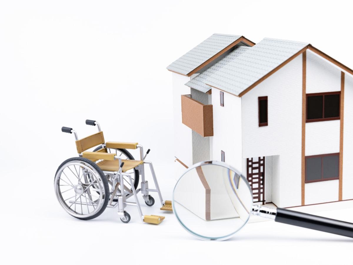 Une chaise roulante devant une maison miniature.